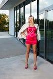 Blonde junge Frau im rosa Kleid und in der weißen Mantelaufstellung Lizenzfreie Stockfotografie