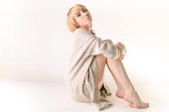 Blonde junge Frau kleidete in der großer weißer Kaschmirstrickjacke und -sitzplätzen auf weißem Ganzboden an Lizenzfreies Stockbild