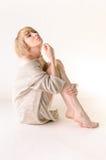 Blonde junge Frau kleidete in der großer weißer Kaschmirstrickjacke und -sitzplätzen auf weißem Ganzboden an Lizenzfreie Stockfotografie