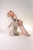 Blonde junge Frau kleidete in der großer weißer Kaschmirstrickjacke und -sitzplätzen auf weißem Ganzboden an Lizenzfreie Stockbilder