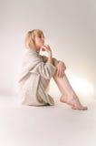 Blonde junge Frau kleidete in der großer weißer Kaschmirstrickjacke und -sitzplätzen auf weißem Ganzboden an Stockfoto