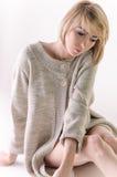 Blonde junge Frau kleidete in der großer weißer Kaschmirstrickjacke und -sitzplätzen auf weißem Ganzboden an Stockbilder