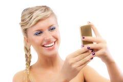 Blonde junge Frau las sms am Telefon Stockbild