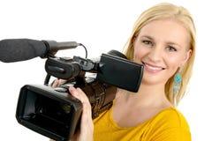 Blonde junge Frau mit Berufsvideokamera, auf Weiß Lizenzfreie Stockfotografie