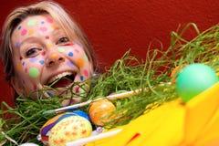 Blonde junge Frau mit bunten Ostereiern Stockbilder