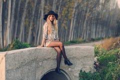 Blonde junge Frau mit dem gelockten Haar in einer Landstraße Lizenzfreie Stockbilder