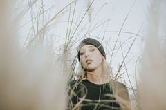 Blonde junge Frau mit einem Knithut an umgeben von den Reedanlagen in der Natur Lizenzfreie Stockfotos