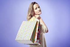 Blonde junge Frau mit Einkaufspapiertüten auf Schulter Ruhiges EM Stockfotos