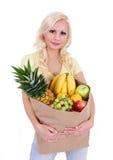 Blonde junge Frau mit Früchten in der Einkaufstasche, getrennt Lizenzfreies Stockbild