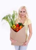 Blonde junge Frau mit Gemüse in der Einkaufstasche Lizenzfreies Stockbild