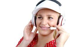 Blonde junge Frau mit Kopfhörer und weißer Kappe Stockfotografie