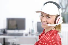 Blonde junge Frau mit Kopfhörer und weißer Kappe Lizenzfreie Stockfotos
