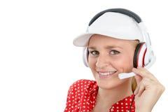 Blonde junge Frau mit Kopfhörer und weißer Kappe Stockfotos
