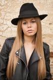 Blonde junge Frau mit schwarzem Hut Stockfotografie