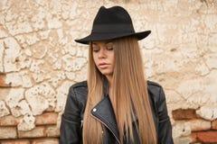 Blonde junge Frau mit schwarzem Hut Stockbilder