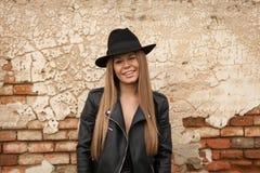 Blonde junge Frau mit schwarzem Hut ein Auge blinzelnd Stockbild