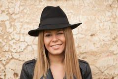 Blonde junge Frau mit schwarzem Hut ein Auge blinzelnd Stockfoto
