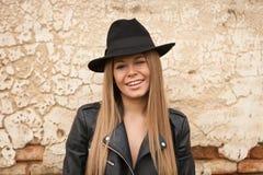 Blonde junge Frau mit schwarzem Hut ein Auge blinzelnd Stockfotos