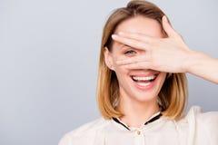 Blonde junge Frau mit strahlendem Lächeln schaut durch ihre Hand Stockfotos