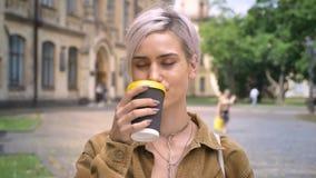 Blonde junge Frau mit trinkendem Kaffee des Durchdringens und des kurzen Haarschnitts und dem Lächeln an der Kamera, stehende nah stock video