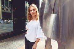 Blonde junge Frau nahe bei der zeitgenössischen Kunst, die Kamera betrachtet Stockbild