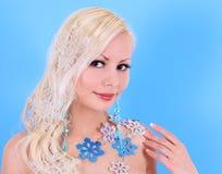 Blonde junge Frau verziert mit Schneeflocken über Blau Stockfotografie