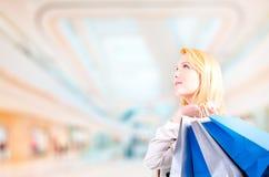 Blonde junge Frau, die Einkaufstaschen in einem Einkaufszentrum aufwärts betrachtet copyspace hält Stockbild