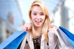 Blonde junge Frau, welche die Einkaufstaschen betrachten abwärts überrascht copyspace in einem Einkaufszentrum hält Lizenzfreie Stockbilder