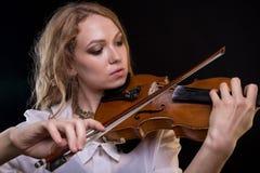 Blonde junge Frau, welche die Violine spielt Lizenzfreies Stockfoto