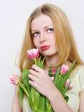 Blonde junge Frauen mit rosafarbenen Tulpen Stockfotos