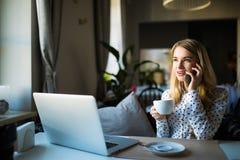 Blonde junge Geschäftsfrau, die ihr Telefon und Laptop an einem Café verwendet Lizenzfreies Stockfoto