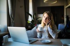 Blonde junge Geschäftsfrau, die ihr Telefon und Laptop an einem Café verwendet Stockbild