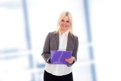Blonde junge Geschäftsfrau mit einem Klemmbrett Stockbild