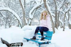 Blonde junge hübsche Frau hat einen Rest auf der Bank in einem Park Lizenzfreie Stockfotografie