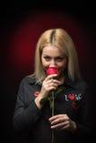 Blonde junge lächelnde riechende Rotrose der Frau Lizenzfreie Stockfotografie