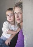 Blonde junge Mutter und ihr Baby nahe einer Wand Lizenzfreies Stockfoto