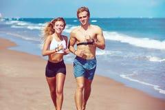 Blonde junge Paare, die auf einem Strand im Sommer laufen Stockfoto