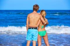 Blonde junge Paare, die den Strand betrachtend stehen Stockbilder