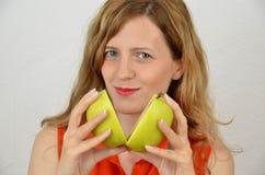 Blonde, junge und sinnliche Frauen mit grünem Apfelschnitt Lizenzfreies Stockfoto