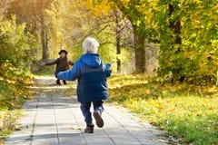 Blonde Jungenläufe, zum ihrer Mutter zu treffen Bäume, die noch mit etwas goldenen Farben grün bleiben Rückseitige Ansicht Stockbild