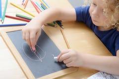 Blonde Jungenzeichnung auf einer Tafel Lizenzfreies Stockfoto