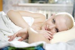 blonde kahle Frau, die auf dem Bett liegt Stockfotos