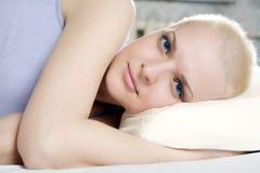 blonde kahle Frau, die auf dem Bett liegt Lizenzfreie Stockfotos