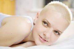 blonde kahle Frau, die auf dem Bett liegt Lizenzfreies Stockfoto