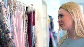 Blonde kaukasische Frau, die bunte Kleidung auf Aufhängern vorwählt stock video