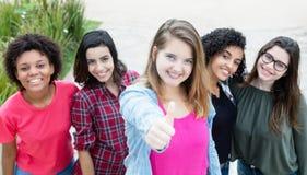 Blonde kaukasische Frau, die Daumen mit Gruppe Freundinnen zeigt Stockfoto