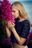 Blonde kaukasische Frau, die dunkelblaues Spitzenoberteil und Weißrock trägt Aufstellung zwischen rosa Blumen und durch das Meer  Lizenzfreies Stockfoto