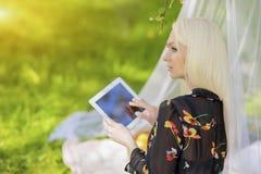 Blonde kaukasische Frau, die Ebook-Tablet-Leser Outside in den Vorderteilen verwendet Lizenzfreie Stockfotos