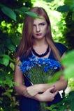 Blonde kaukasische Frau, die einen Kornblumeblumenstrauß hält Lizenzfreie Stockfotos