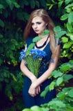 Blonde kaukasische Frau, die einen Kornblumeblumenstrauß hält Stockfoto